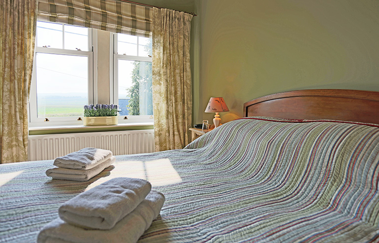 The pretty bedroom weavers cottage has views out to the rolling hills of otterburn, holiday cottages in otterburn, wedding venue otterburn, le petit chateau otterburn, accommodation for weddings otterburn, otterburn cottages