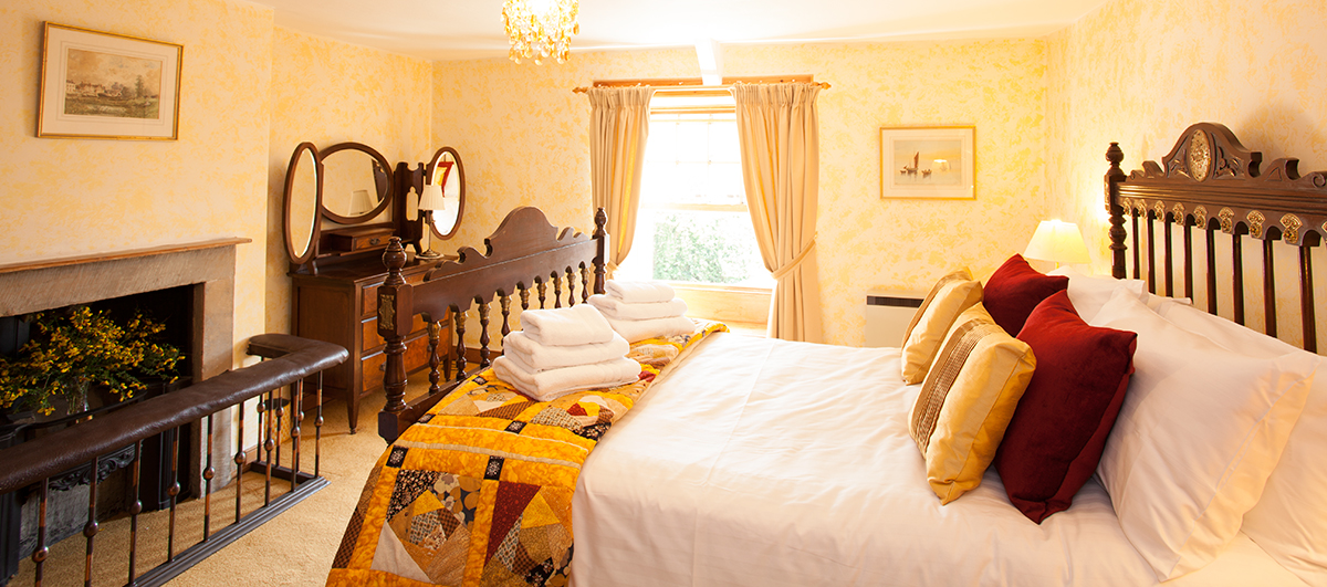 the master bedroom at Border House is spacious with original fireplace, the house sleeps 7 and welcomes 3 well behaved dogs with a huge enclosed garden